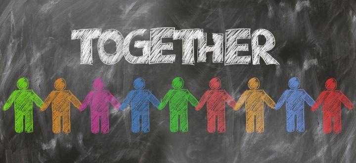 -Together - bunte, gemalte Kreidemenschen auf Schiefertafel